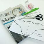 Abb. SG 1: Ihr braucht: die Schablone, eine Zeitungseite, einen Falzstift (oder Kugelschreiber), Klebeband, Lineal , Schere, sehr dünnen Draht